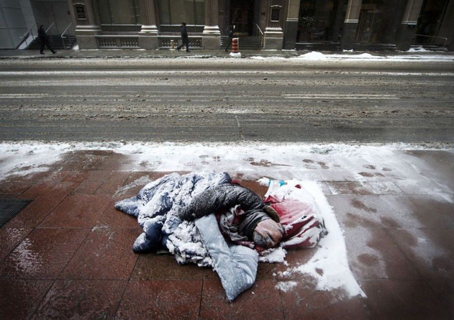 Homeless person sleeping on the side of the road surrounded by snow
