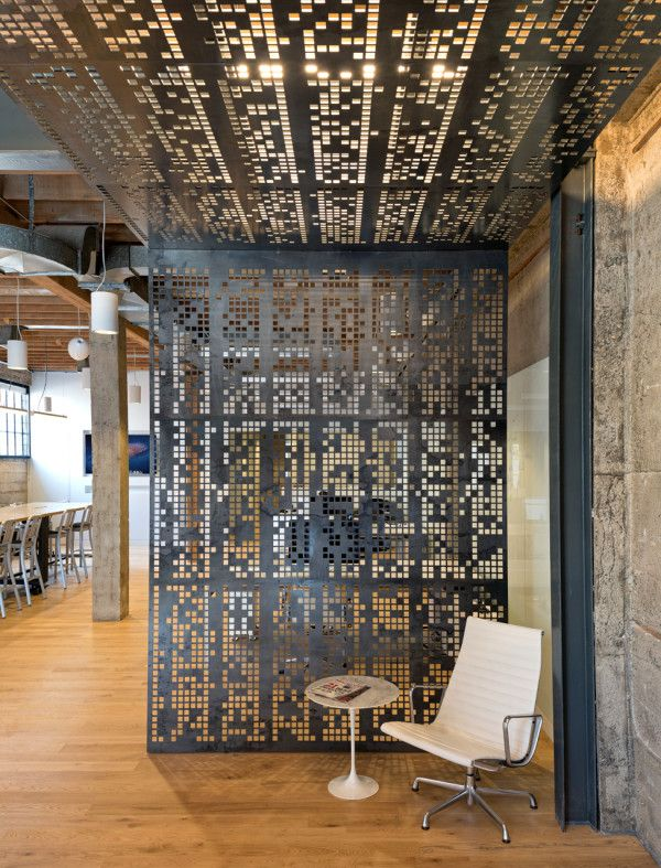 "Giant Pixel Office by Studio O+A. ""At the office's entrance, a blackened steel canopy was installed to create a separation between the reception and waiting areas and the office space. The canopy is perforated with a computer code pattern that looks like random pixels."""