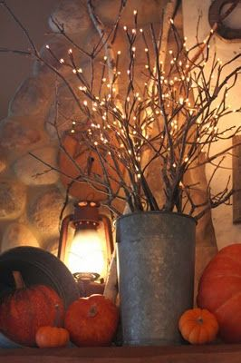 buy a minimum of l.e.d. lighted branches (they come in a box at target), add a few real branches (for more fullness) in a rustic container, with rocks in the bottom to hold the shape of the arrangement: