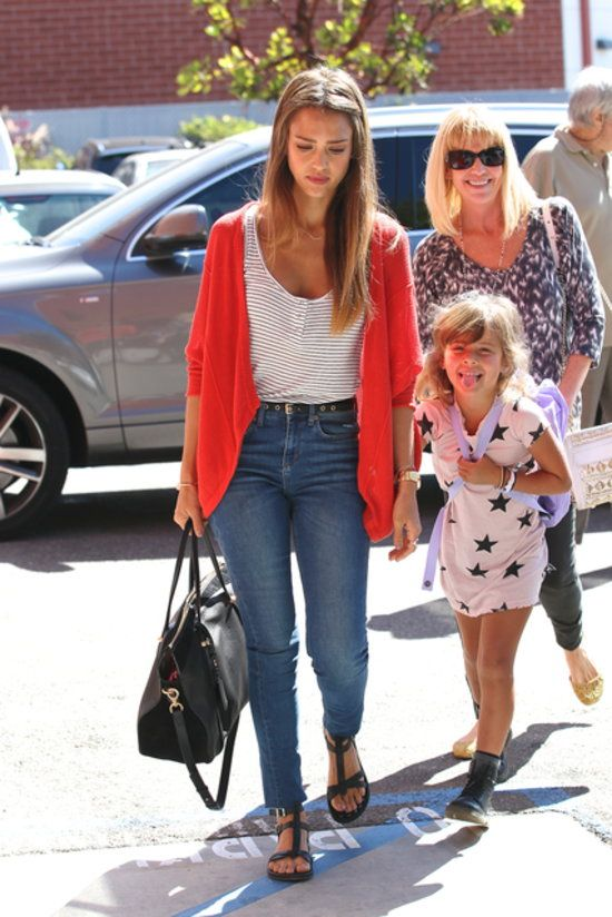 50 Unparalleled Street Style Looks Courtesy of Jessica Alba: Jessica tucked a white tee into floral denim, then spiced things up with a coral bag in West Hollywood. : Even on a casual coffee run in LA, Jessica looked stylish in brown riding boots, a black Bulgari bag, and tortoise sunglasses. : Jessica Alba rocked a pair of high-waisted jeans with a striped tank and a red cardigan in LA.:
