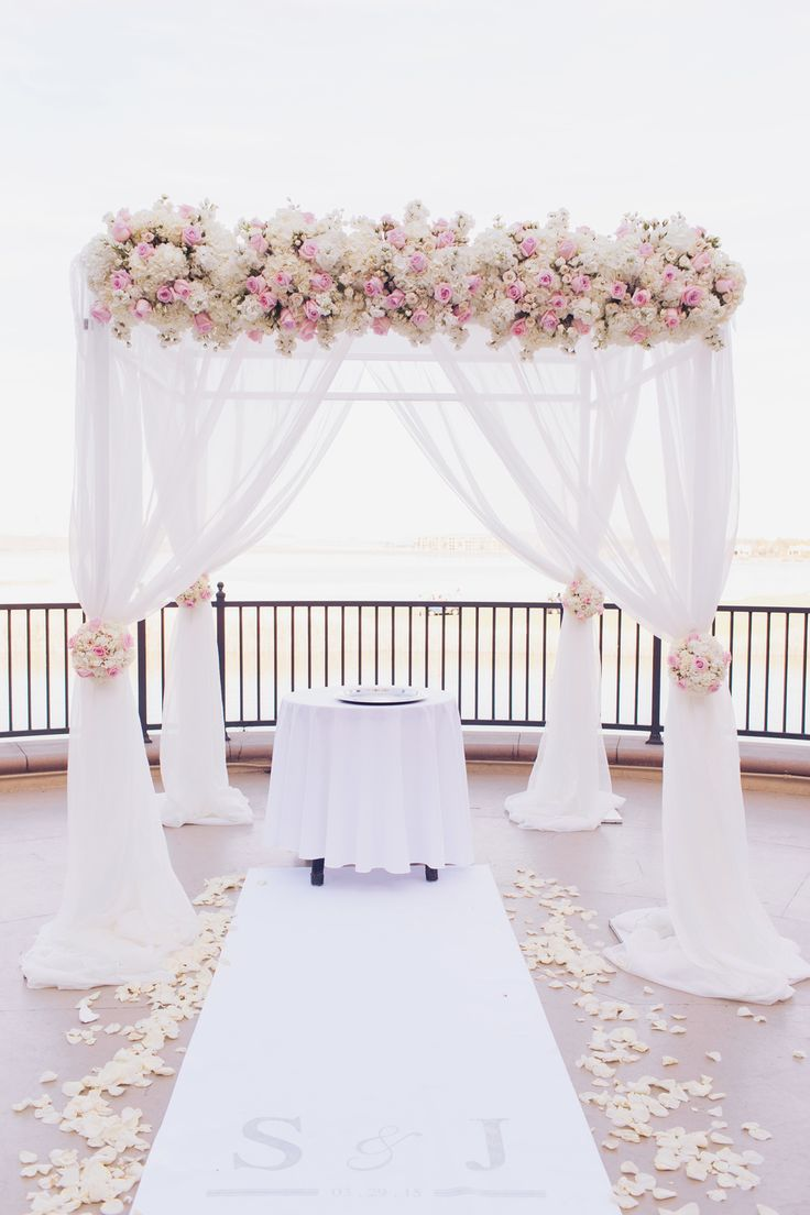 For the lakeside ceremony we dressed a chuppah in flowing ivory fabric topped with ivory and pale pink roses.  Matching topiaries