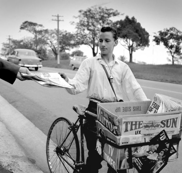 Newspaper boy on bicycle, with The Sun and Daily Mirror ...