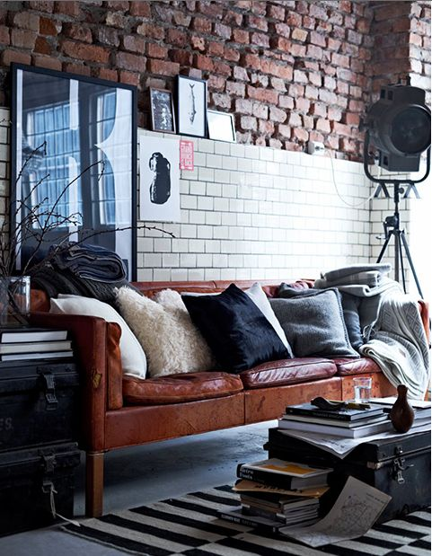 Great vintage cognac leather sofa displayed in front of an exposed brick wall. Works well!