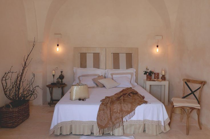 Bedroom at Masseria Le Carrube in Puglia, Italy with white and beige linens, stucco walls.