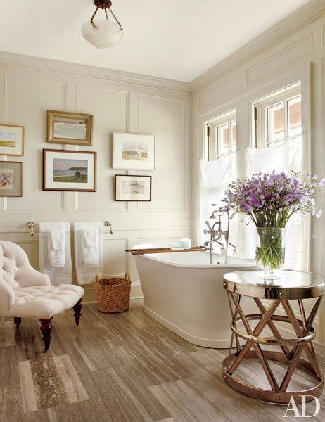 Paintings of Long Island are grouped in Susan's bath; the side table is from Homenature, and the tub fittings are by Perrin & Rowe.: