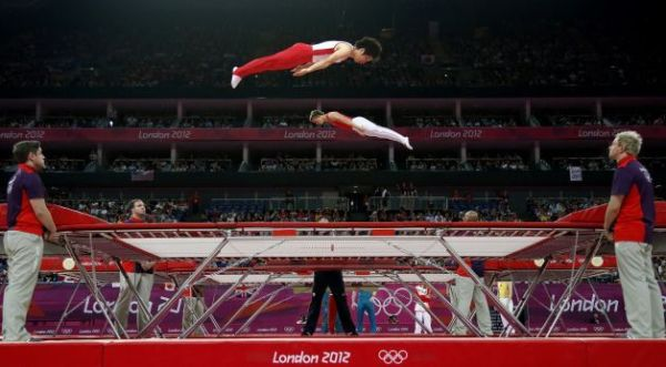 Gymnasts train before the men's trampoline final of the ...