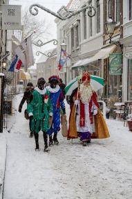 Sinterklaas met zwarte pieten in de sneeuw