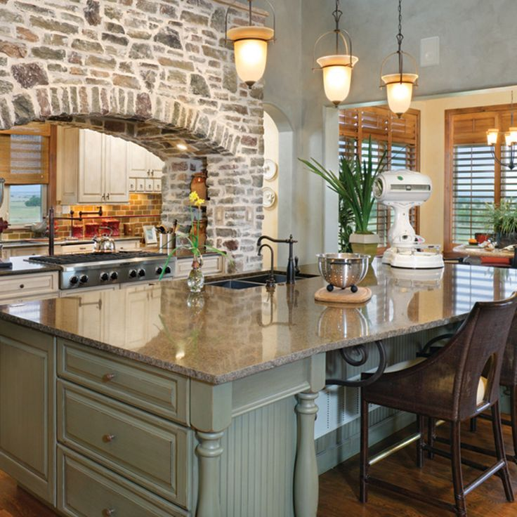 Rustic Kitchen With Brick Arch And Double Sided Stove