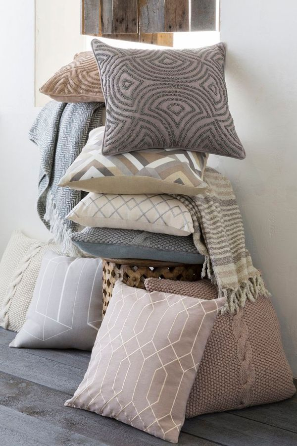 Stack of unique neutral and muted color Surya pillows in a ...