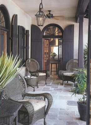 Grey flagstone floor, French doors with grey shutters and grey rattan furniture. Just