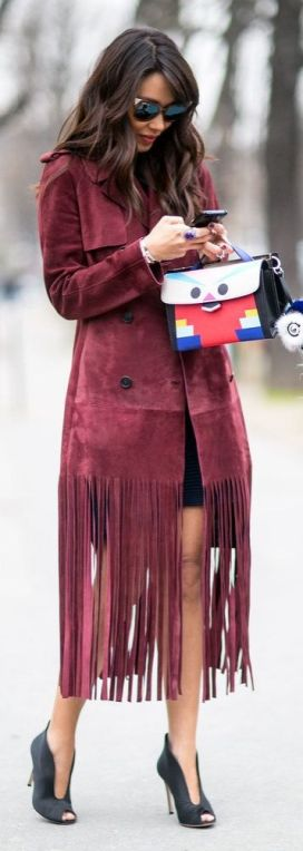 Paris Fashion Week street style inspiration: a wine red fringe suede jacket with a cartoon Fendi purse and black open-toed pumps: