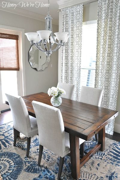 Love the contrast of the dark table against the white chairs and blue and white rug.: