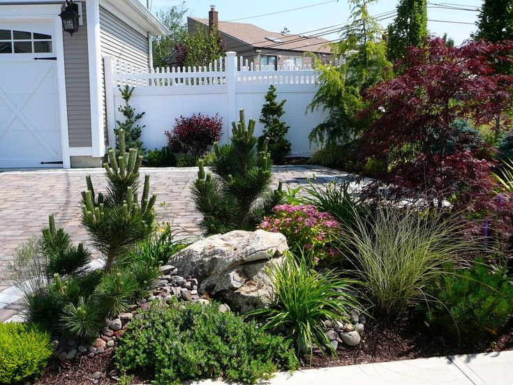 A Landscaped Bed With Ornamental Grass Evergreens And A