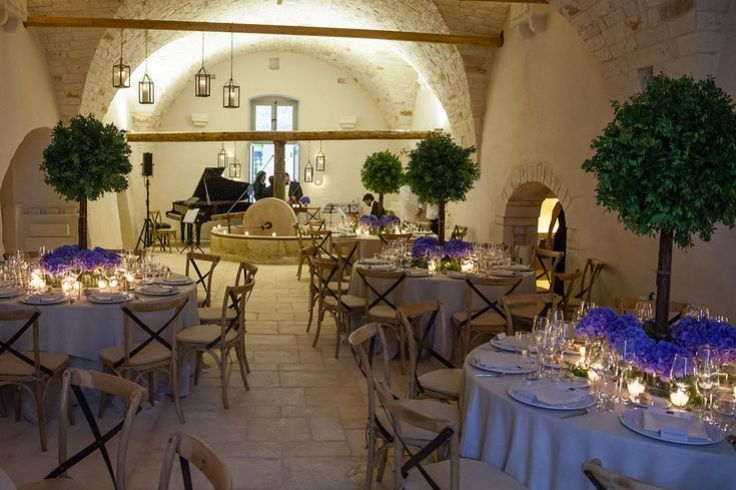 Dining room at Masseria Le Carrube in Puglia, Italy with white tablecloths, arched ceiling and candle light
