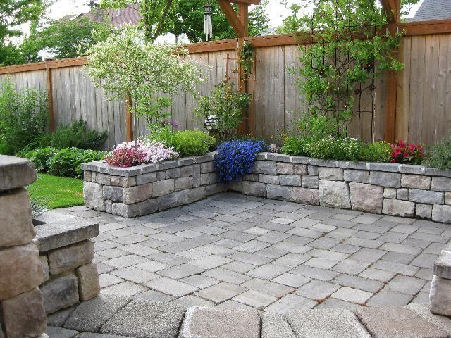 Stone Patio With Stone Planter Or Bench Around Perimeter