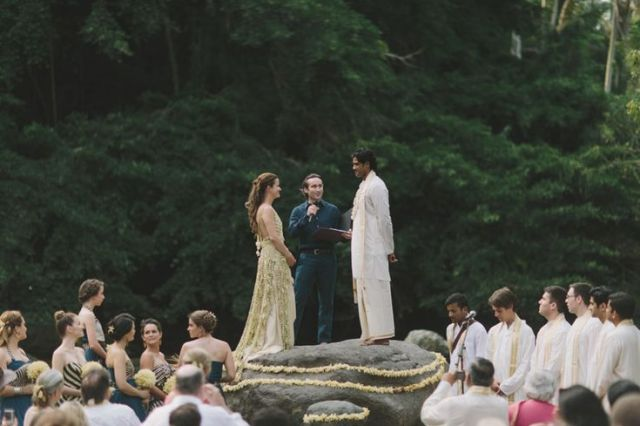 A bride and groom standing on a rock in Australia during their wedding party.
