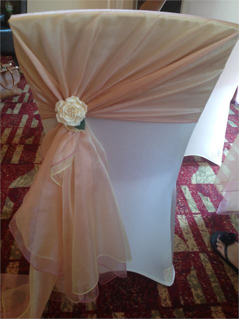 Ivory Chair Cover With Gold And Dusky Pink Organza Sash Tied On The Side With A Rose Wedding