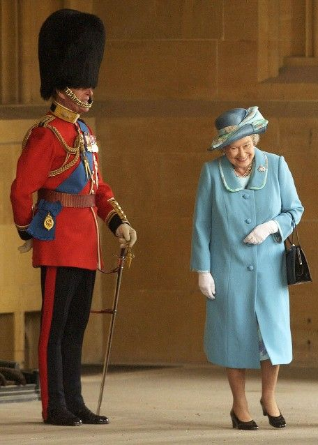 Queen Elizabeth laughing as she passes her husband, Prince Philip, Duke of Edin