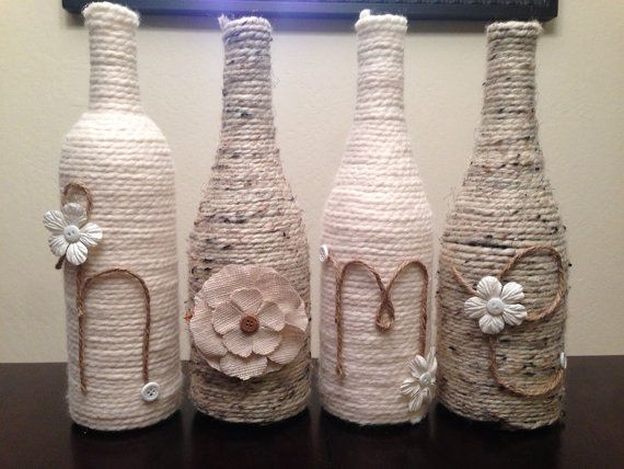 These up cycled wine bottles are delicately wrapped in neutral colored yarn then adorned with buttons and flowers to say either