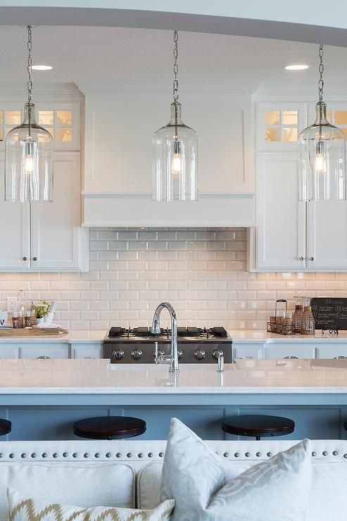 A trio of Corsica Pendants illuminate an extra long kitchen island topped with white quartz fitted …