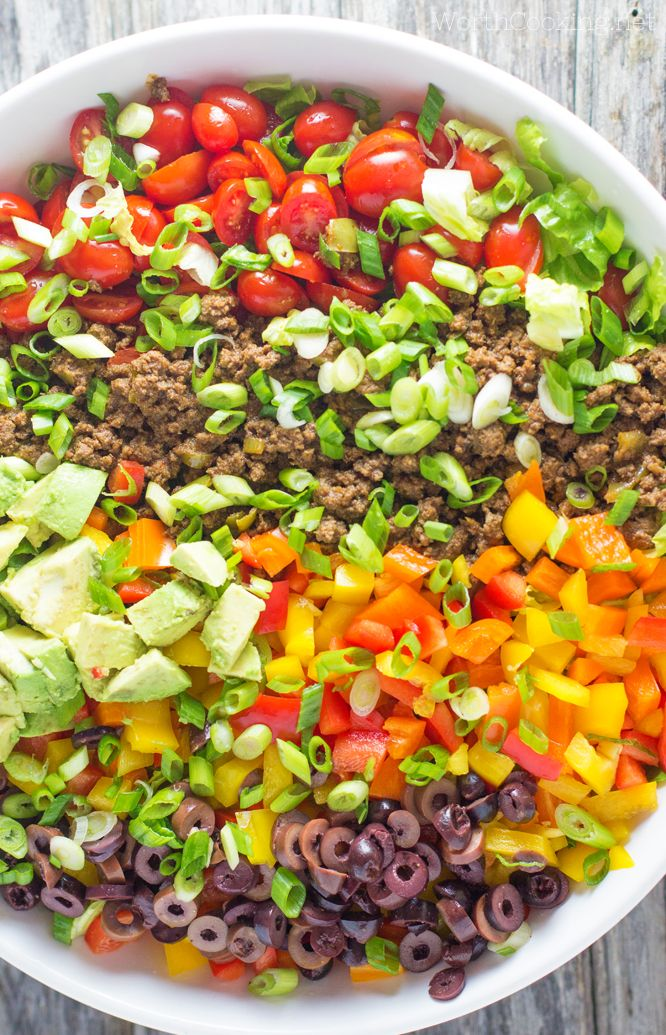 A colorful taco salad full of fresh vegetables, and seasoned meat. Plantain chips add a nice crunch without the corn, and it is