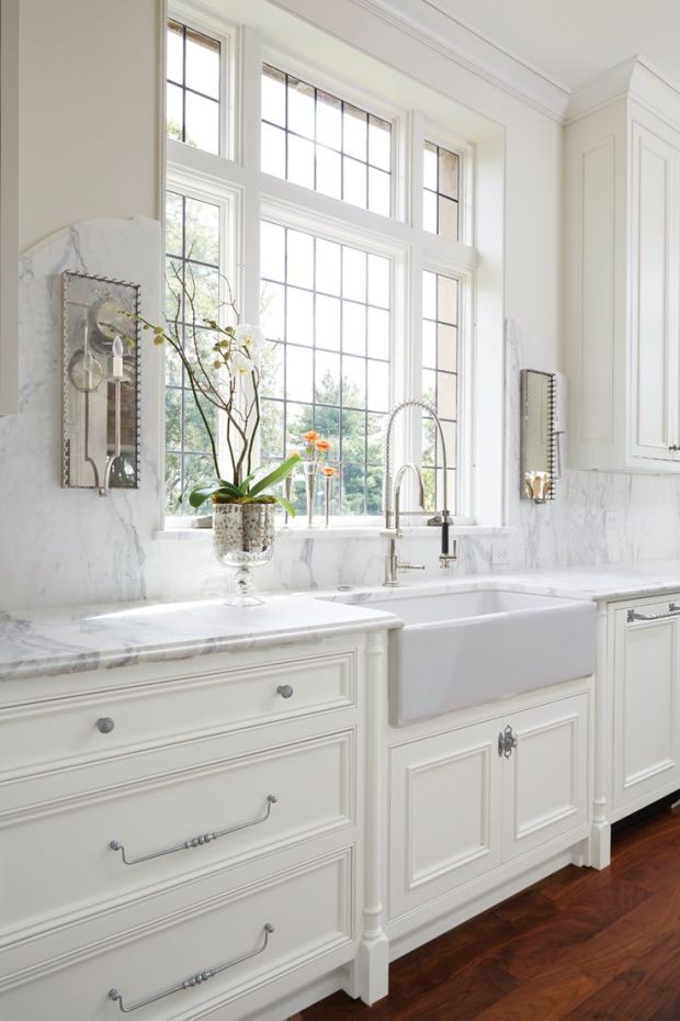 White + marble kitchen. Not those sconces, farm/apron sink, or hardware. Large window. Wide drawers.: