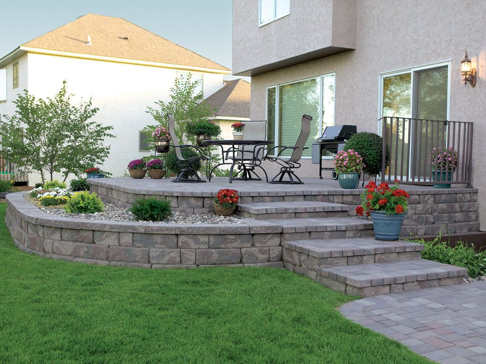 A raised patio featuring the Highland Stone Retaining Wall ... on Patio Stone Wall Ideas id=25922