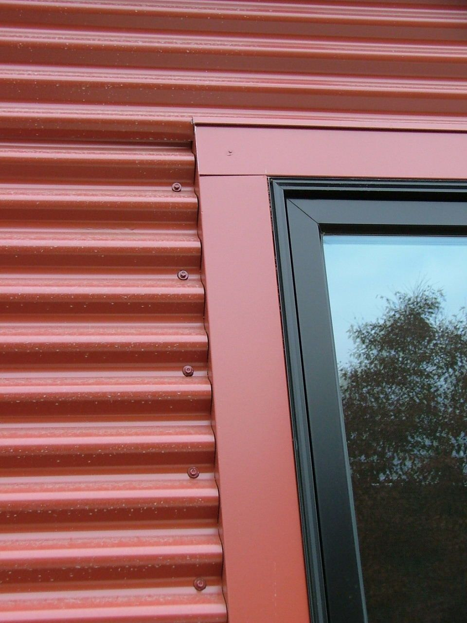 Detail with window frame corrugated steel siding