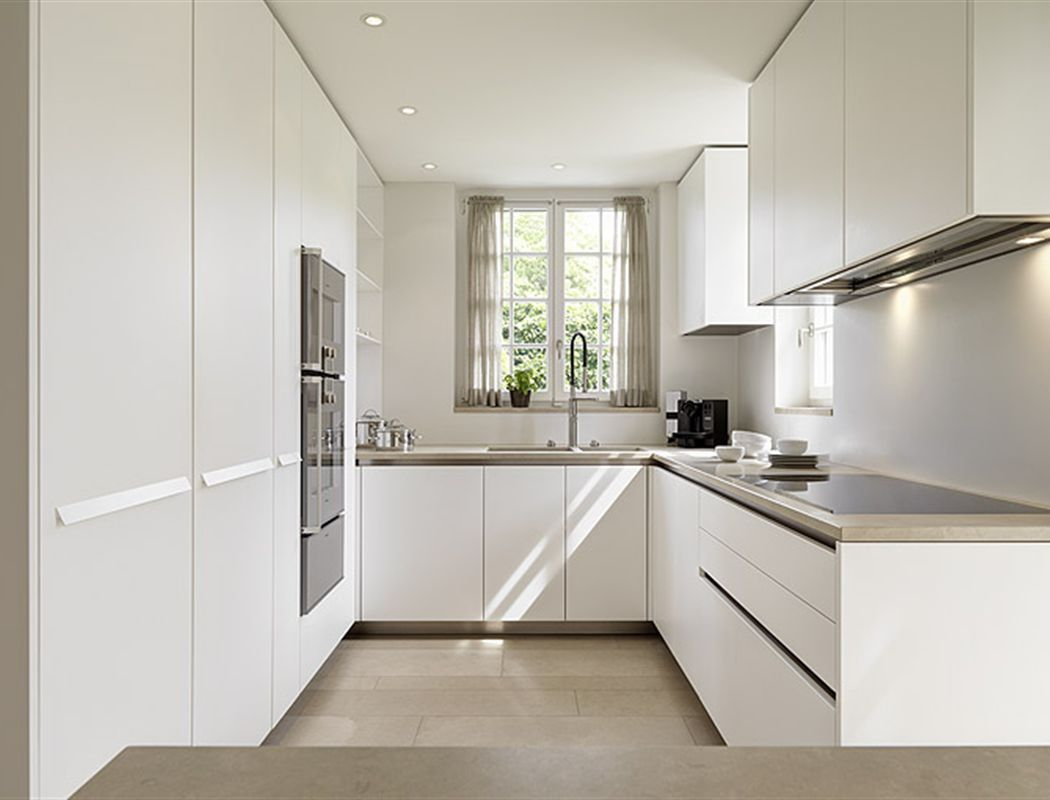 The layout of this open kitchen is unique, in which it occupies 2 parallel walls for the main cabinets, while the dining area is placed right in between the two cabinets, as there is a large floor space available. 9 Modern and Best U Shaped Kitchen Designs with Images