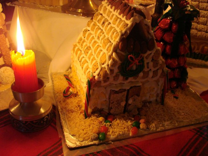 A candle burning brightly to illuminate a little gingerbread house