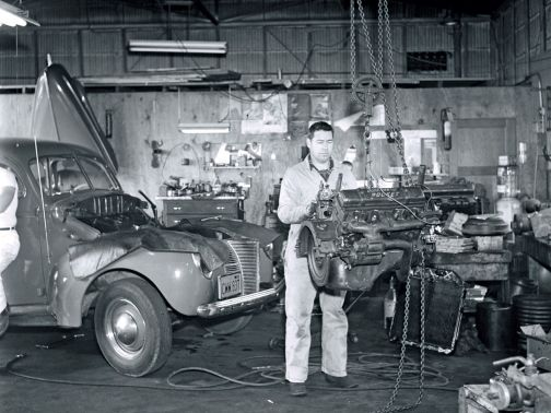 Black and white vintage photo of a mechanic fixing an engine in a messy garage