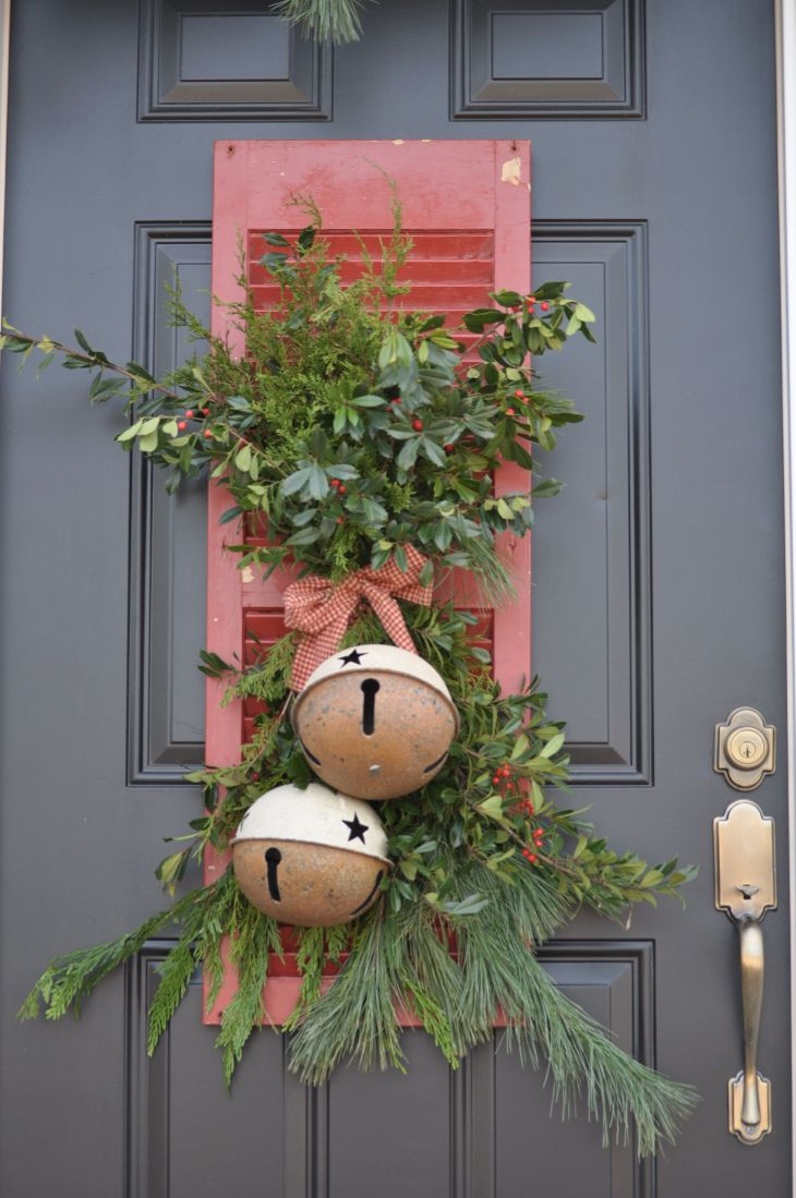 Christmas door decor with bells and an old shutter  Christmas