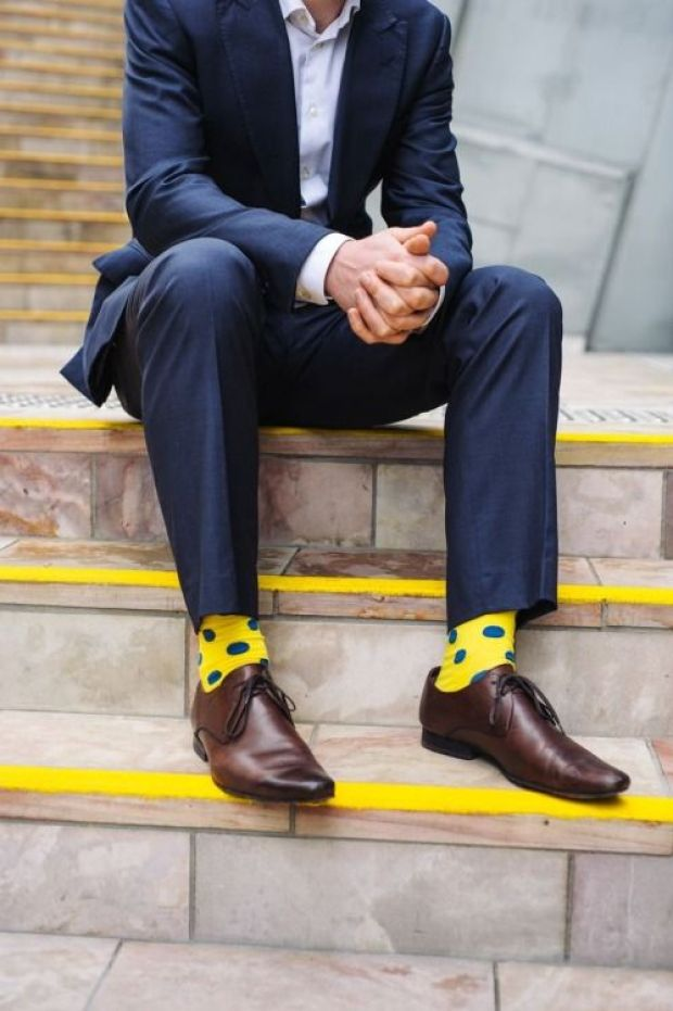 Men sitting on stairs, wearing bright yellow dotted socks