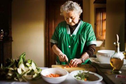 Imagen de una anciana cortando unos vegetales en una cocina