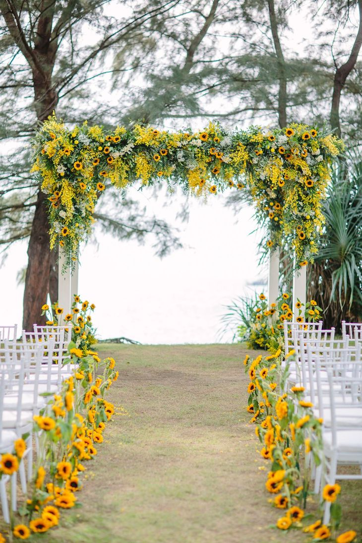 Yellow wedding ceremony backdrop and aisle decor with sunflowers