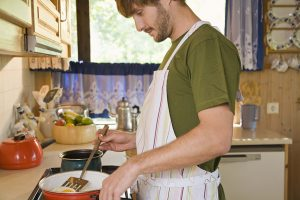 Man wearing apron and cooking food