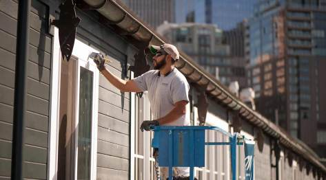 A painter works on the Seattle Aquarium at Pier 59 on Puget Sound