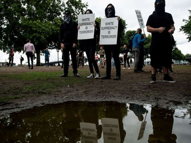 PHOTO: Black-clad protesters, gathered to oppose conservative groups staging an End Domestic Terrorism rally, hold signs in Portland, Ore., on Saturday, Aug. 17, 2019.