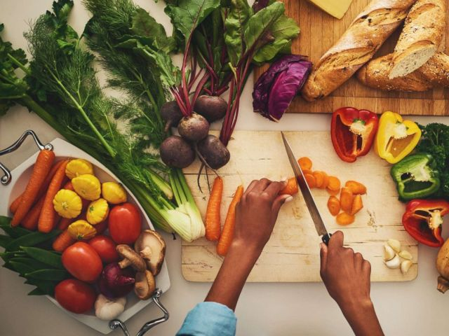 PHOTO: A person chops vegetables on a cutting board in the kitchen at home in an undated stock photo.