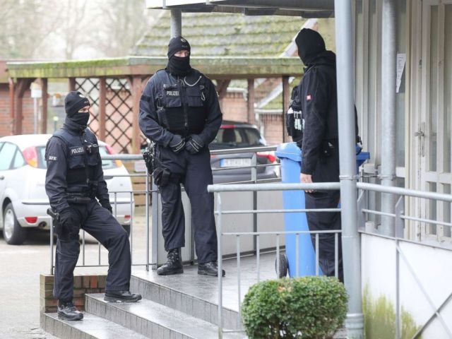 PHOTO: Police officer stand in front of at building during a raid in the village Meldorf, Germany, Jan. 30, 2019.