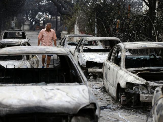 A man passes burned cars in Mati, east of Athens, Tuesday, July 24.