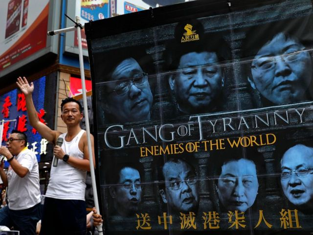 PHOTO: In this June 9, 2019, file photo, protesters display a banner with images of Chinese President Xi Jinping during a march along a downtown street against the proposed amendments to an extradition law in Hong Kong.