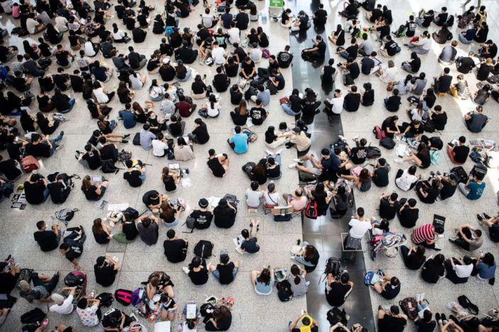 PHOTO: Hong Kong protesters sit during another demonstration at Hong Kongs international airport, Aug. 13, 2019.