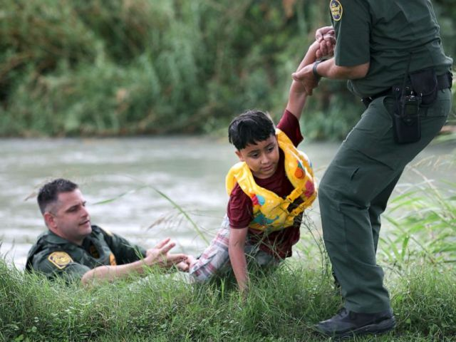 PHOTO: Border Patrol Agent in Charge Eagle Pass, Bryan Kemmett, left, passes a 7-year-old boy from Honduras to another agent after he was rescued from the swollen Rio Grande River, near Eagle Pass, Texas, May 10. 2019.