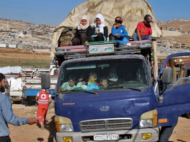 PHOTO: Syrian refugees ride a truck carrying their personal belongings at a Lebanese army checkpoint in Wadi Hmeid in the Bekaa valley, after leaving the village of Arsal to return to their homes in Syrias Qalamoun region on July 23, 2018.