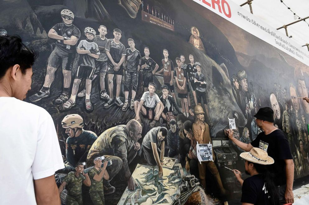 PHOTO: Local artists work on a mural dedicated to the successful rescue of the Wild Boars football team outside an art gallery in Chiang Rai province, July 18, 2018, as family members await for the childrens homecoming.
