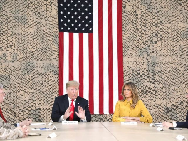 PHOTO: President Donald Trump, flanked by National Security Adviser John Bolton, first lady Melania Trump and U.S. Ambassador to Iraq Doug Silliman, meets political and military leaders during an unannounced visit to Al Asad Air Base, Iraq, Dec. 26, 2018.