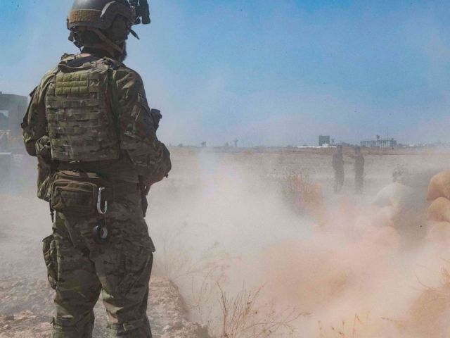 PHOTO: A U.S. service member oversees members of the Syrian Democratic Forces as they demolish a YPG fortification in northeast Syria, Sept. 21, 2019.