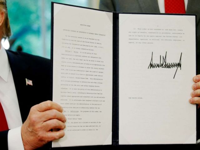 PHOTO: President Donald Trump displays an executive order on immigration policy after signing it in the Oval Office at the White House in Washington, June 20, 2018.