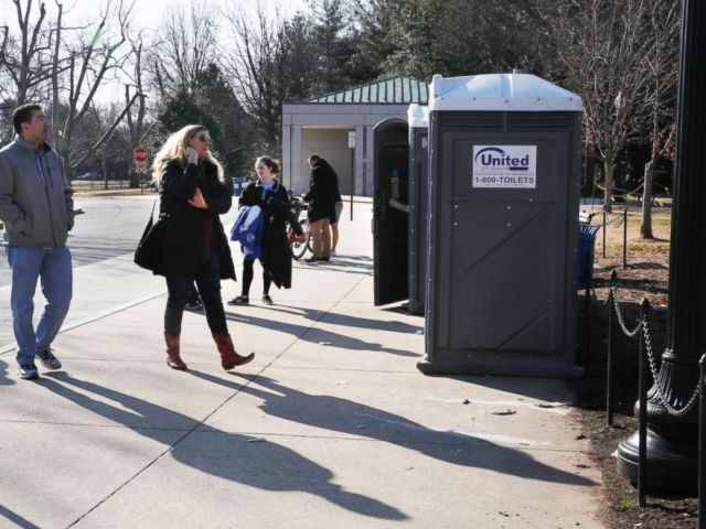 PHOTO: With the regular bathrooms closed during the government shutdown, tourists wait in line for port-a-potties while visiting the World War II Memorial, Dec. 26, 2018, in Washington.
